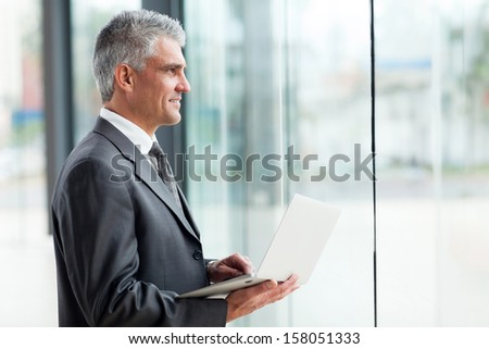thoughtful middle aged businessman with laptop computer - stock photo