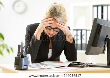 thoughtful middle-aged businesswoman analyzing reports in office - stock photo