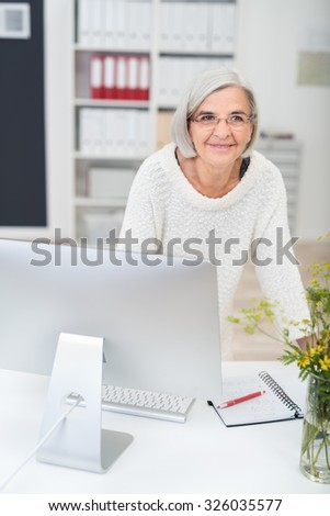 Thoughtful Middle Aged Businesswoman Leaning Against her Desk In the Office and Looking Into the Distance. - stock photo