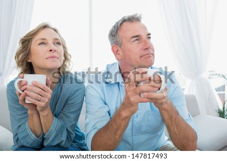Thoughtful middle aged couple sitting on the couch having coffee looking away at home in the living room - stock photo