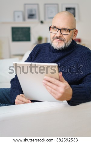 Thoughtful middle-aged man relaxing at home on a couch in the living room holding a tablet computer and looking off to the side with a contemplative expression - stock photo