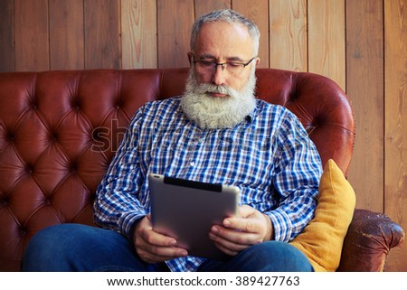 thoughtful middle-aged man with tablet pc resting on sofa at home - stock photo