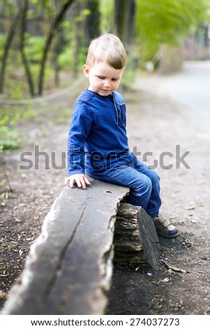 Thoughtful pensive little boy sitting on a wooden bench in a park - stock photo