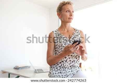Thoughtful powerful mature professional business woman in an office space, sitting on her desk and using a smartphone, workplace interior. Senior businesswoman using technology. - stock photo