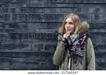 Thoughtful pretty blond girl standing in front of a textured grey brick wall with her hand to her chin staring pensively up into the air with copy space - stock photo