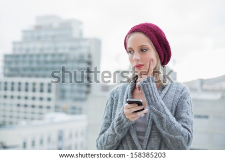 Thoughtful pretty blonde text messaging outdoors on urban background - stock photo