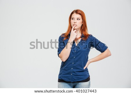 Thoughtful pretty redhead young woman standing and thinking over white background - stock photo