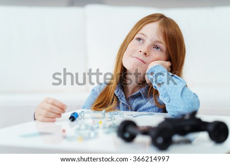 Thoughtful pretty young redhead girl sitting at a table daydreaming looking up into the air with a serious pensive expression - stock photo