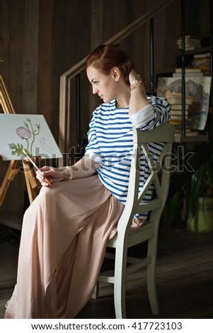 Thoughtful pretty young redhead woman artist thinking near her painting in studio - stock photo