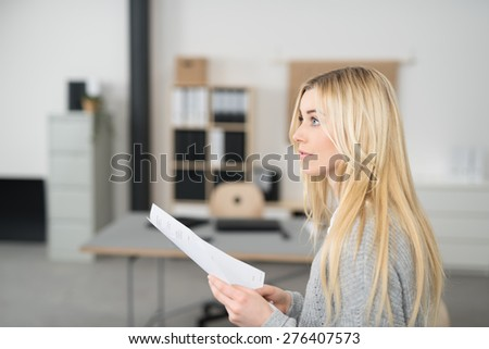 Thoughtful Pretty Young Woman with Long Blond Hair Holding a Paper Inside the Office While Looking to the Upper Left of the Frame, Captured in Side View. - stock photo