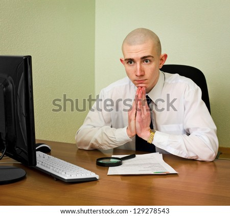 Thoughtful puzzle office manager sits at table with documents and computer - stock photo