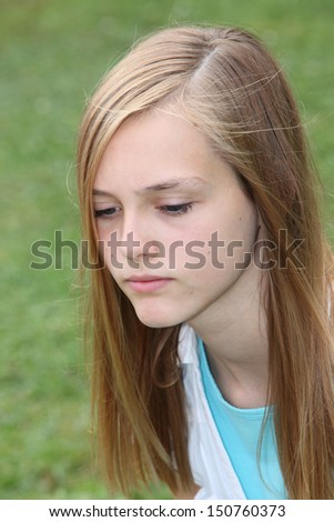 Thoughtful sad teenage girl with a serious expression and downcast eyes, closeup head portrait outdoors against grass - stock photo