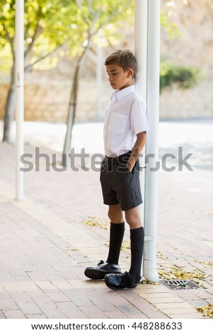 Thoughtful schoolboy leaning on pole with hands in pocket in school corridor - stock photo