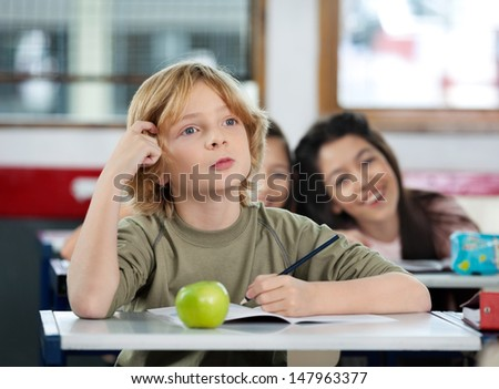 Thoughtful schoolboy scratching his head while looking away at desk in classroom - stock photo