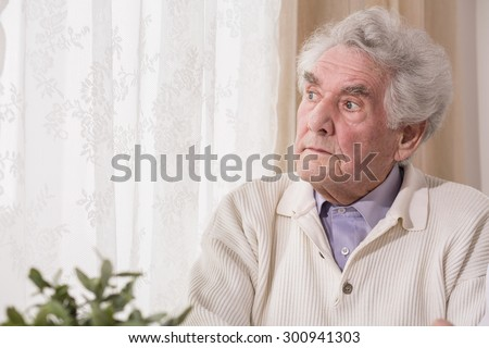 Thoughtful senior man looking at the window - stock photo