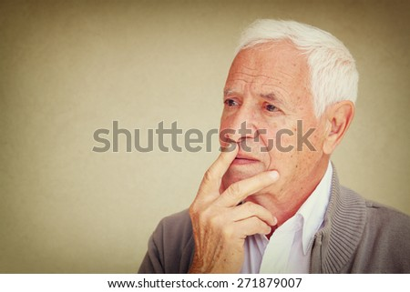 Thoughtful senior man looking up into the air as he stands against a blank textured wall with copyspace  - stock photo