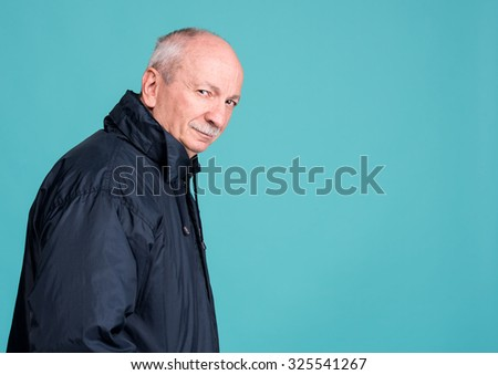 Thoughtful senior man on a blue background with copy space - stock photo