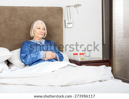 Thoughtful senior woman relaxing on bed at nursing home - stock photo