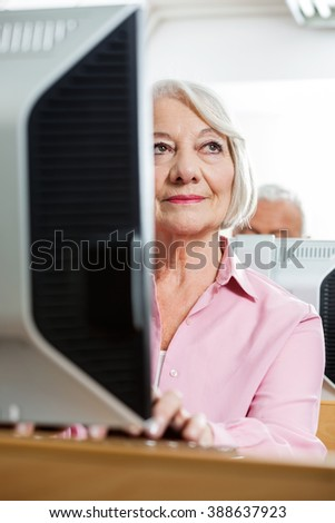 Thoughtful Senior Woman Using Computer In Classroom - stock photo