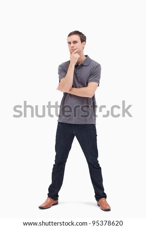 Thoughtful standing man with his legs apart against white background - stock photo