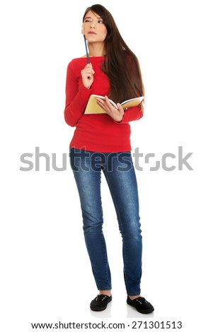 Thoughtful student woman with notebook and pen. - stock photo