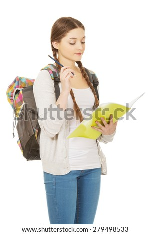 Thoughtful teenage girl with school backpack holding folders. - stock photo