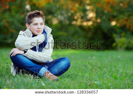 thoughtful teenager boy in green park - stock photo