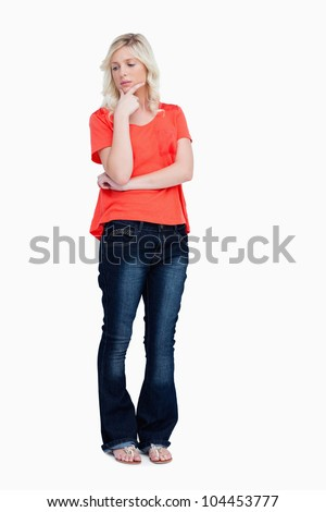 Thoughtful teenager standing upright with fingers on chin against a white background - stock photo