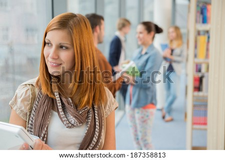 Thoughtful university student with classmates in background at library - stock photo