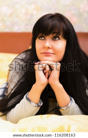 Thoughtful woman in bed. Selective focus on eyes. - stock photo