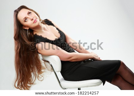 Thoughtful woman in black dress sitting on the office chair over gray background - stock photo