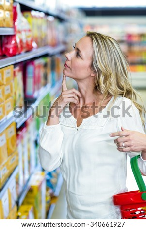 Thoughtful woman looking at shelves in the supermarket - stock photo