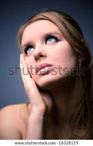 Thoughtful woman looking up. On dark background. - stock photo
