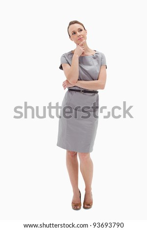 Thoughtful woman posing in dress against white background - stock photo
