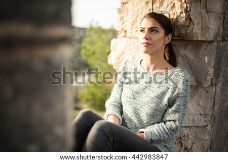 Thoughtful woman sitting alone outdoors.Daydreaming and imagining.Overcoming depression and anxiety problems.Optimistic person expression.Reflecting on past.Relaxing walk in nature.Stress relief - stock photo