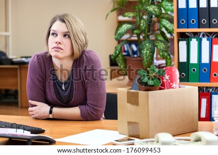 Thoughtful woman sitting in the office with the collected personal things in a box - stock photo