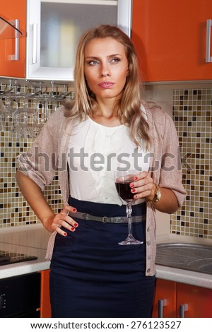 thoughtful woman with a glass of red wine in kitchen - stock photo