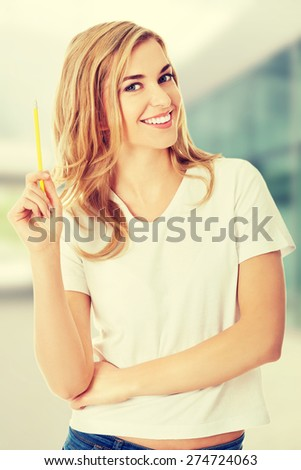 Thoughtful woman with pencil in her hand - stock photo