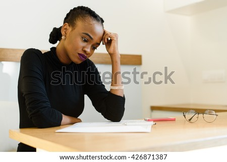 Thoughtful worried African or black American woman holding her forehead with hand looking at notepad in office - stock photo