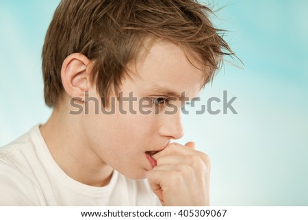 Thoughtful worried young boy biting his nails in trepidation as he stares at the ground with a serious expression, profile head shot on blue with copy space - stock photo