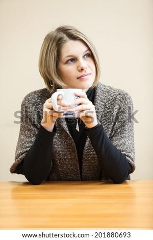 Thoughtful yong woman drinking coffee - stock photo