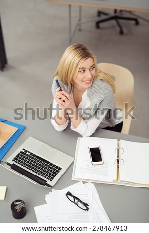 Thoughtful Young Blond Girl Sitting at her Worktable with Laptop, Mobile Phone and Notes, Looking to the Right of the Frame, Captured in High Angle View. - stock photo