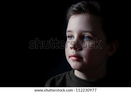 Thoughtful young boy in a dark lowkey portrait - stock photo