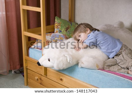 Thoughtful young boy with polar bear soft toy lying on bunk bed - stock photo