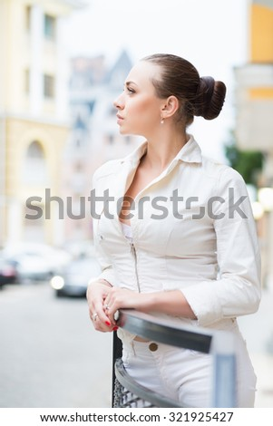 Thoughtful young brunette wearing white jacket posing outdoors - stock photo