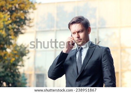 Thoughtful young businessman in suit and tie talking on the mobile phone while standing outdoors with office building in the background - stock photo