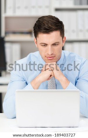 Thoughtful young businessman sitting at his desk reading his laptop screen with his chin resting on his hands as he concentrates on the information, frontal view - stock photo