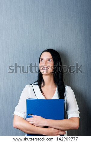 Thoughtful young businesswoman holding binder against blue wall - stock photo