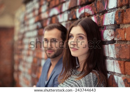 Thoughtful young couple standing leaning against a face brick wall covered in graffiti watching to the left of the frame - stock photo