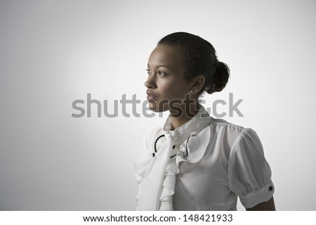 Thoughtful young elegant woman looking away against gray background - stock photo